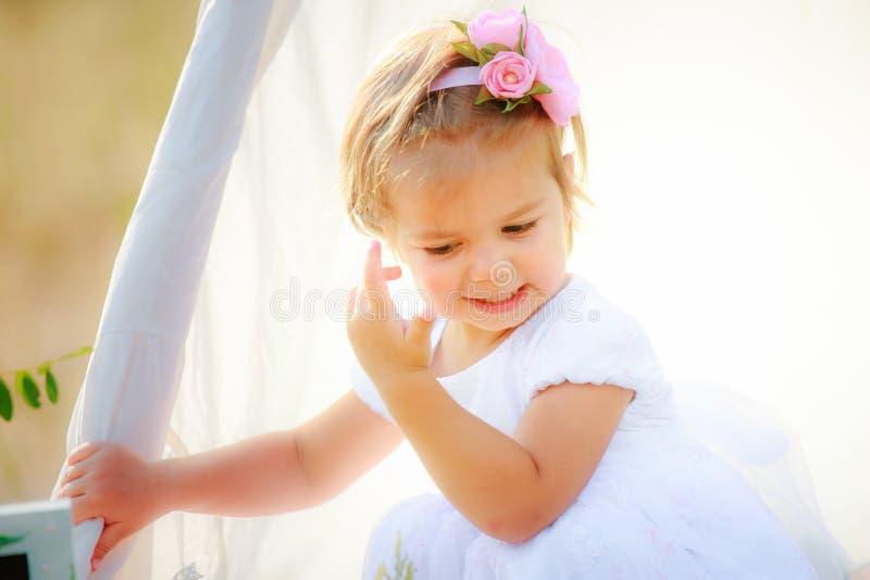 Маленькая девочка регулирует ее волосы хаты для игр Ребенок с красивым стилем причёсок в белом платье стоковые фотографии rf