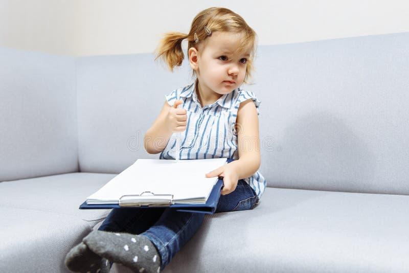 Маленькая девочка рисует ручкой на бумаге стоковые изображения rf