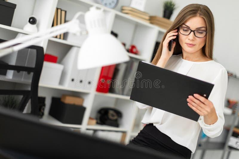 Маленькая девочка сидела вниз на таблице в офисе, держа таблетку с листами в ее руке и говоря на телефоне стоковая фотография