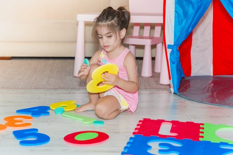 Маленькая девочка сидит и держит красочная циновка игры головоломки стоковое изображение