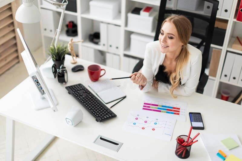 Маленькая девочка сидит на столе компьютера в офисе, держа карандаш в ее руке и работая с документами стоковые изображения rf