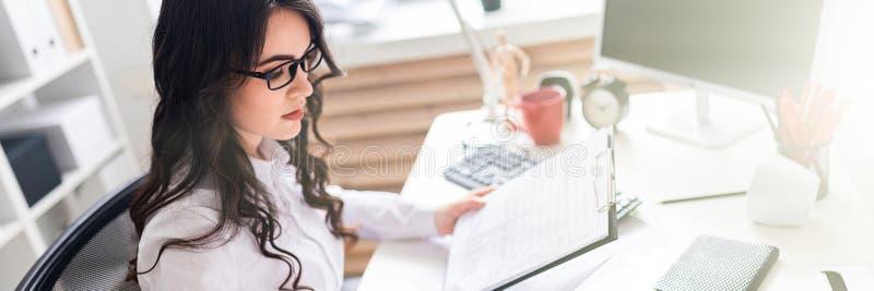 Маленькая девочка сидит на столе офиса и проверяет документы стоковое фото rf