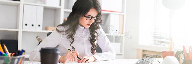 Маленькая девочка сидит на таблице офиса, держит ручку в ее руке и смотрит документы стоковая фотография rf
