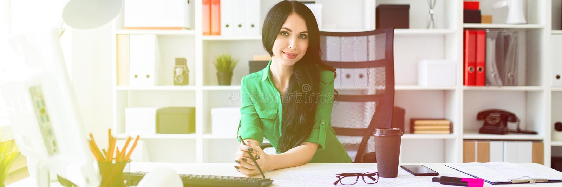 Маленькая девочка сидит на таблице офиса и держит карандаш в ее руках стоковые изображения