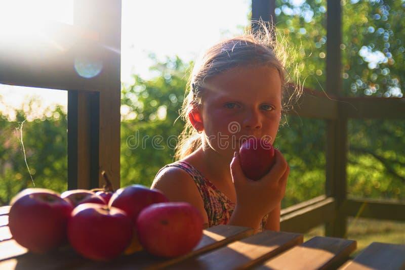 Маленькая девочка сидит на таблице на verandah и eatting свежих яблоках Яблоки на таблице Мечтательное и романтичное изображение стоковая фотография