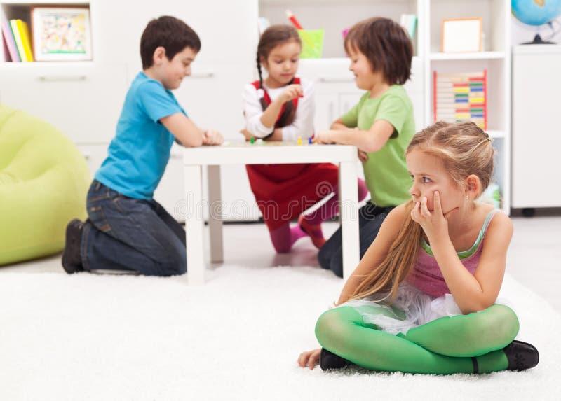 Маленькая девочка сидя врозь - ощупывание исключенное другими стоковое фото