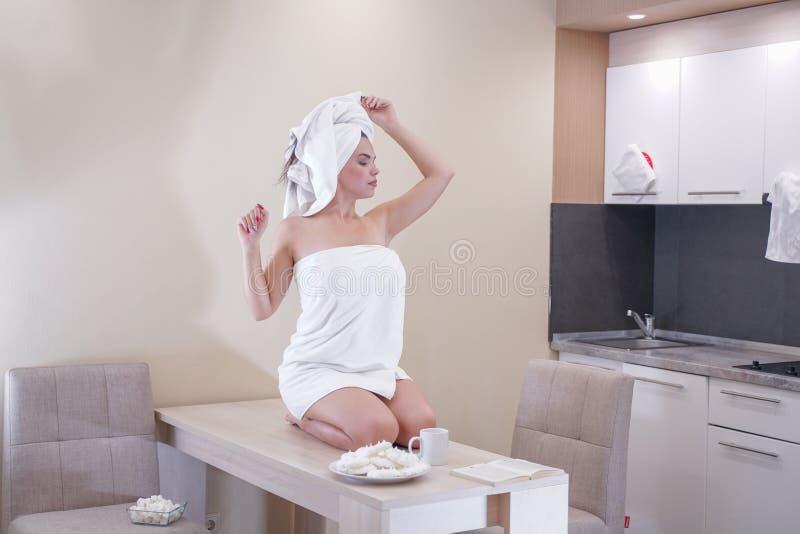 Маленькая девочка сидя в кухне после ливня в оболочке в белых полотенце и отдыхать стоковая фотография