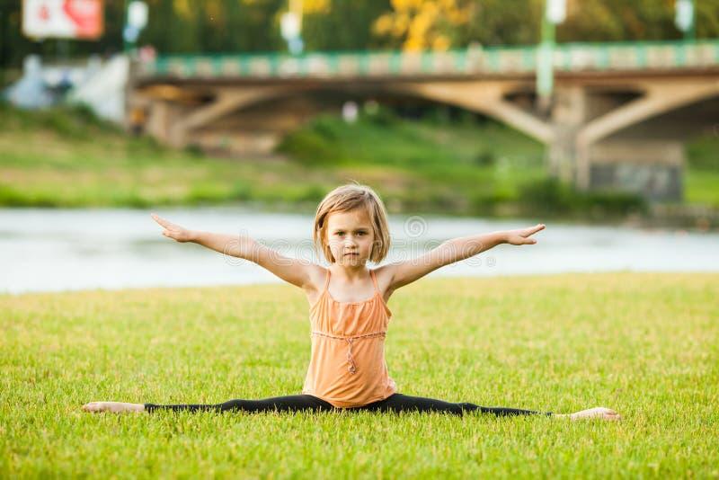 Маленькая девочка сидя в представлении разделения на траве стоковое изображение