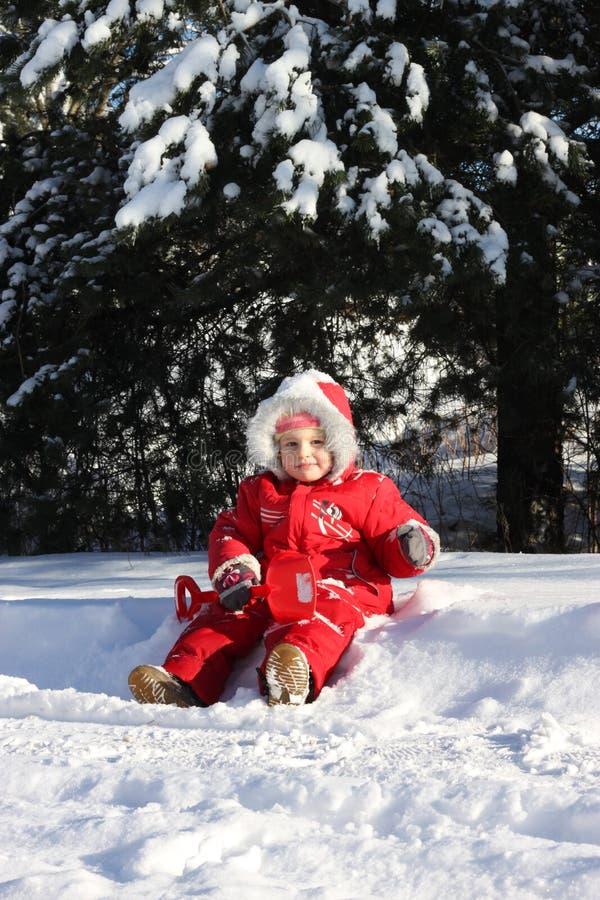 Маленькая девочка сидя в снеге стоковые фотографии rf