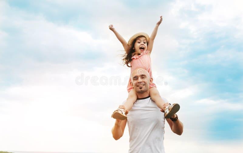 Маленькая девочка сидя на плечах ` s отца стоковое изображение