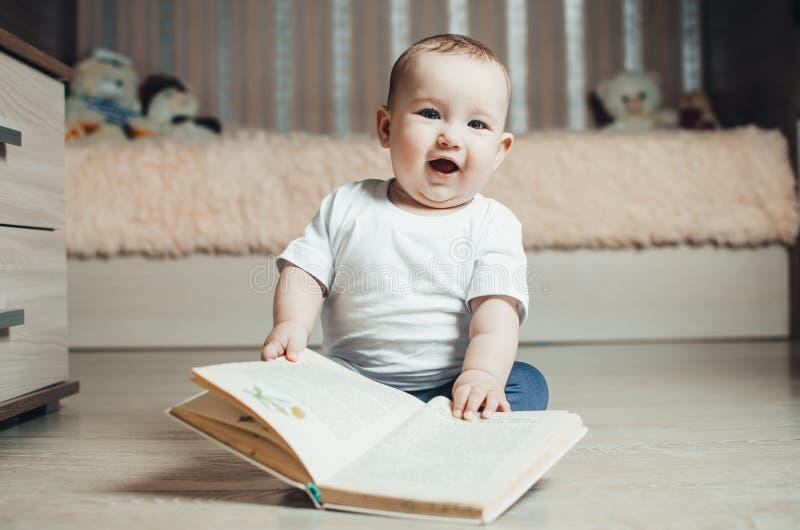 Маленькая девочка сидя на поле с книгой стоковое фото