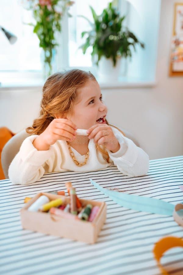 Маленькая девочка сидя на таблице в atelier и играя с потоками стоковые фотографии rf