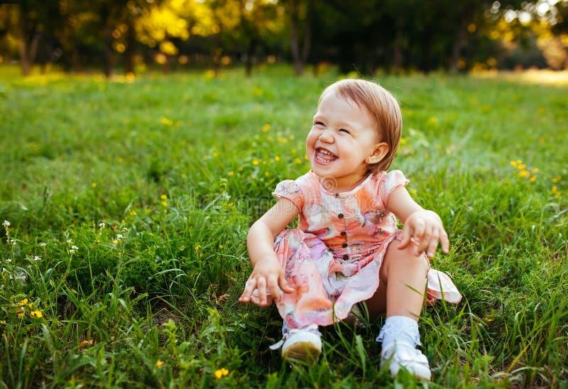 Маленькая девочка сидя на траве в парке стоковое изображение