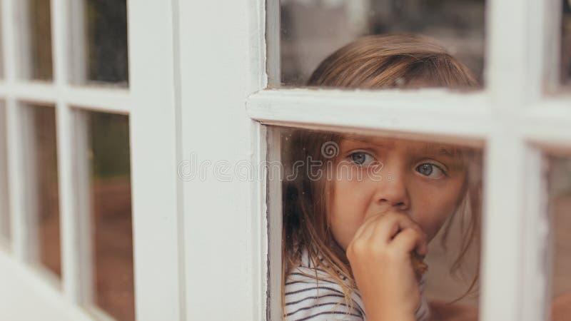 Маленькая девочка сидя окном стоковые фотографии rf