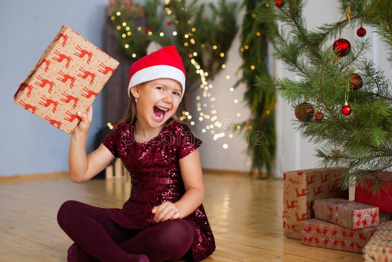 Маленькая девочка сидя около рождественской елки с подарком в ее руках стоковые изображения rf