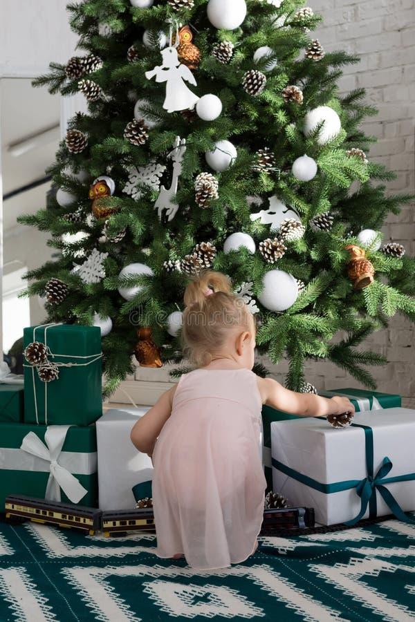 Маленькая девочка сидя около рождественской елки стоковое изображение rf