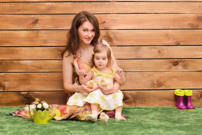 маленькая девочка сидя с мамой и цыпленоками стоковые изображения