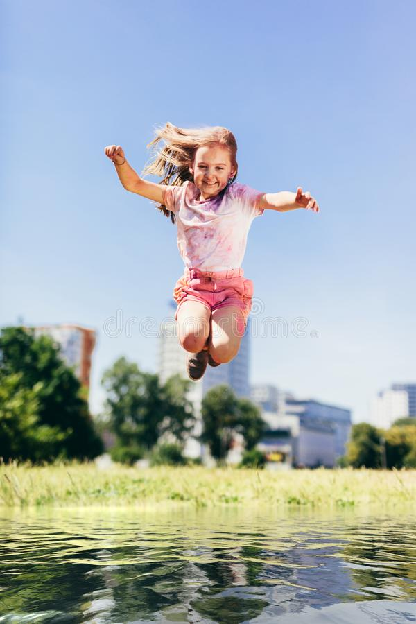 Маленькая девочка скача высоко над большой лужицей воды стоковое фото