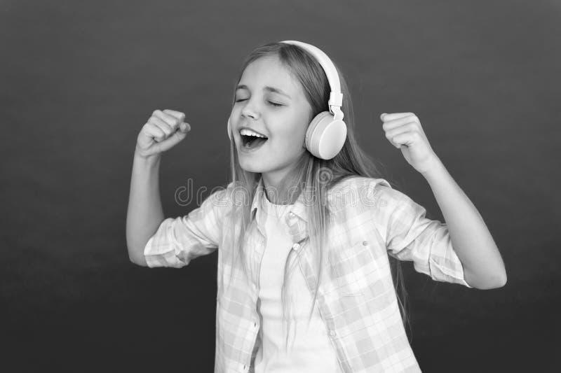 Маленькая девочка слушает наушники песни Онлайн канал радиостанции Ребенок девушки слушает наушники музыки современные Получите м стоковое изображение rf