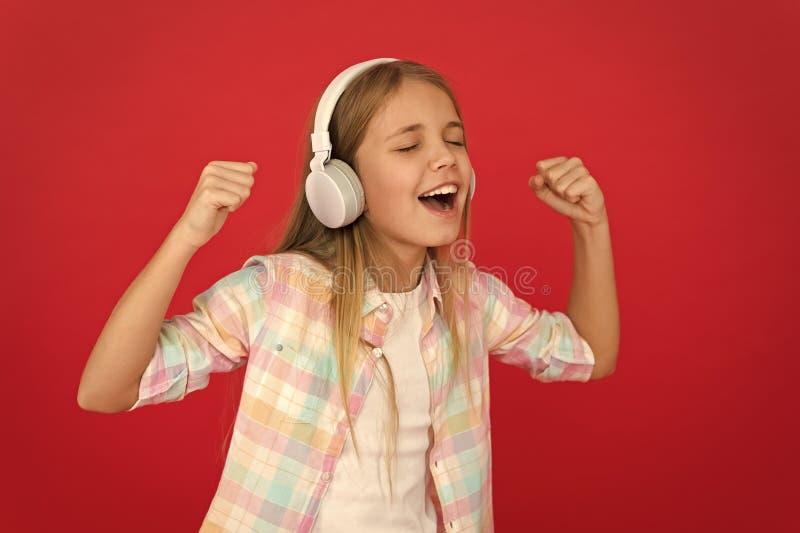 Маленькая девочка слушает наушники песни Онлайн канал радиостанции Ребенок девушки слушает наушники музыки современные Получите м стоковая фотография