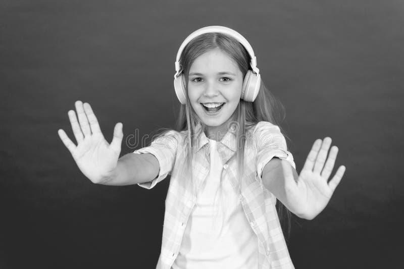 Маленькая девочка слушает наушники песни Онлайн канал радиостанции r Ребенок девушки слушать музыка современная стоковые изображения rf