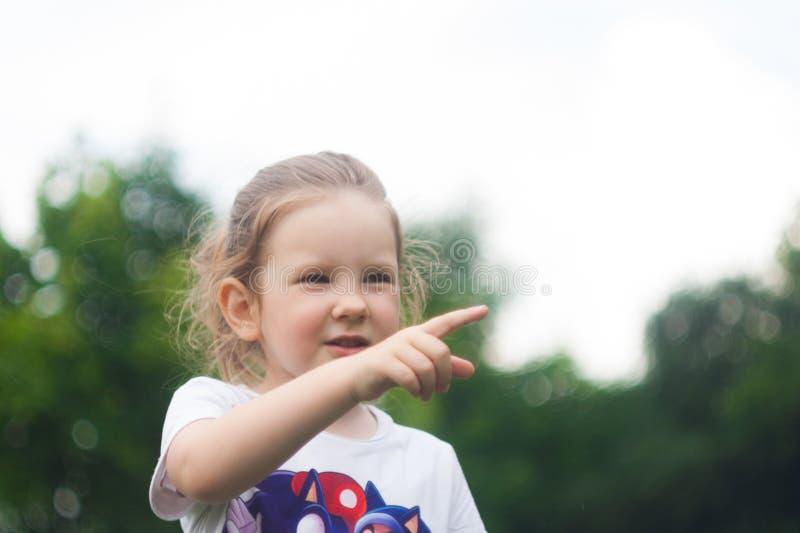 Маленькая девочка смотрит в расстояние, говорит что-то и указывает палец стоковое фото rf