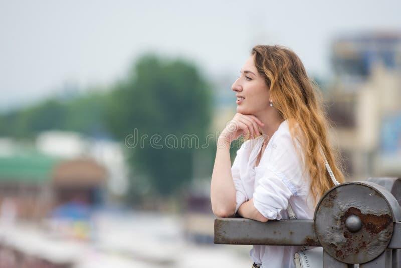 Маленькая девочка смотрит в склонность расстояния на старой загородке стоковое фото rf