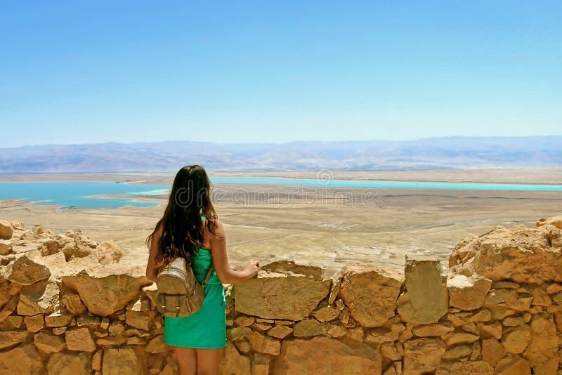 Маленькая девочка смотрит мертвое море Руины замка Herods в крепости Masada в Израиле стоковое изображение