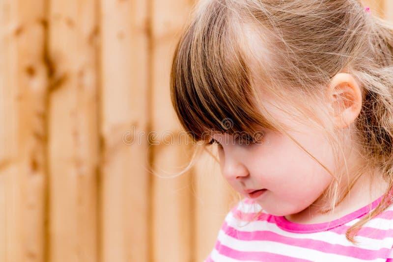 Маленькая девочка смотря вниз созерцательно стоковые фото