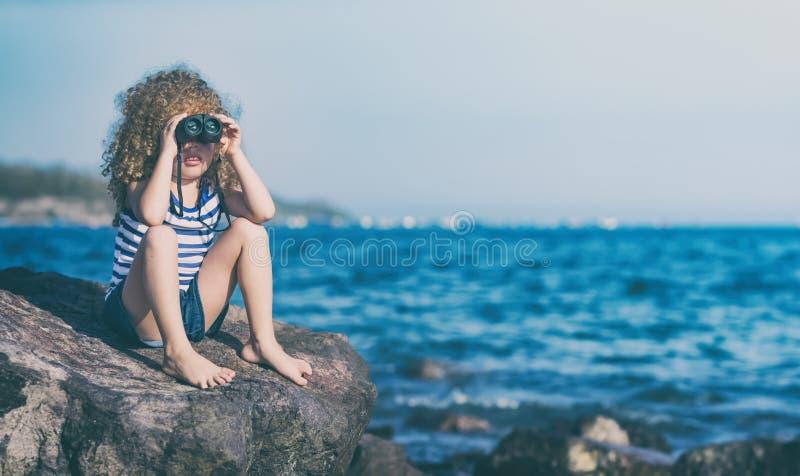 Маленькая девочка смотря далеко с биноклями стоковая фотография rf