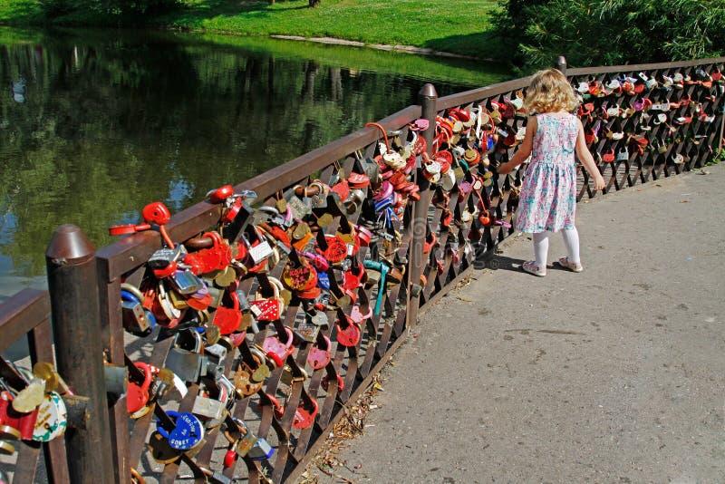 Маленькая девочка смотря свадьбу фиксирует дальше обнести ботанический сад названный Tsitsin в Москве стоковые фото