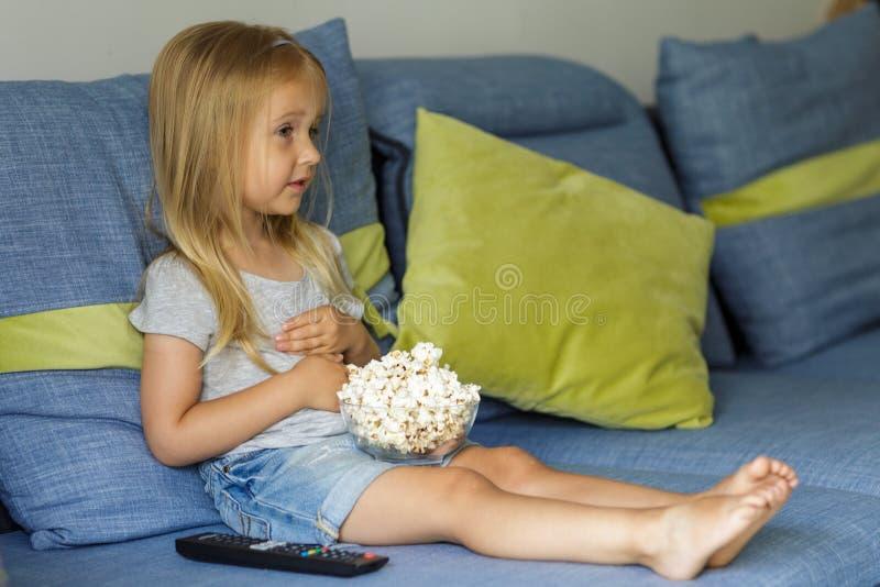 Маленькая девочка смотря ТВ Счастливая милая маленькая девочка держа шар с попкорном стоковое фото