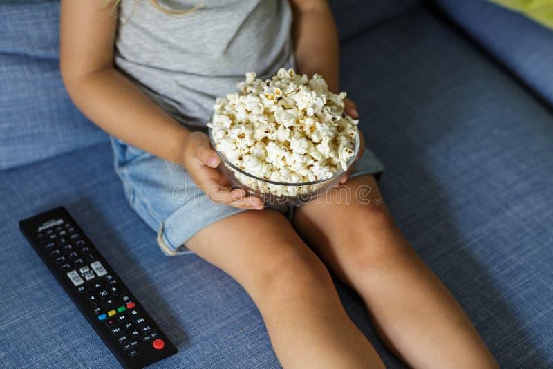 Маленькая девочка смотря ТВ Счастливая милая маленькая девочка держа шар с попкорном стоковые фотографии rf