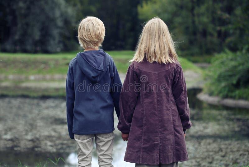 Маленькая девочка со светлыми волосами и мальчиком в синем пиджаке стоя назад на береге реки и смотря на парке стоковые фото