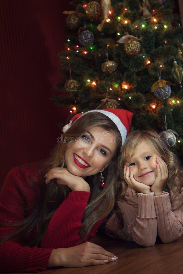 Маленькая девочка со своей мамой в окружении Рождества стоковое изображение rf