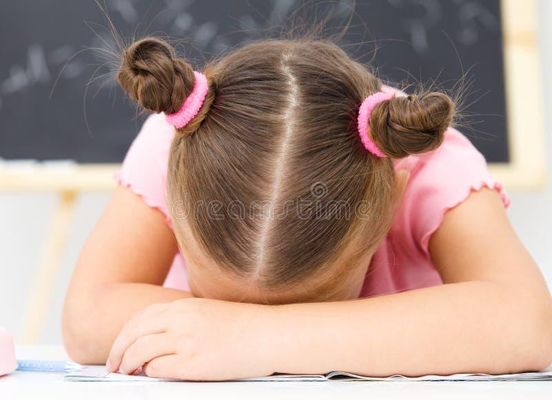 Маленькая девочка спит на ее сочинительств-книге стоковая фотография