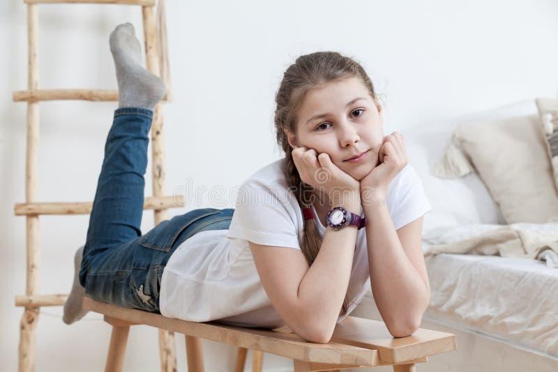 Маленькая девочка спокойствия кладя на деревянную скамью в спальне около кровати, одела белую футболку и голубые джинсы стоковое изображение rf