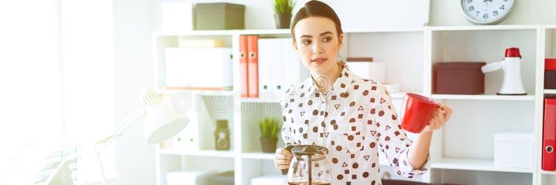 Маленькая девочка стоит в офисе около таблицы, держа чайник в ее руке и держа вне чашку стоковые изображения