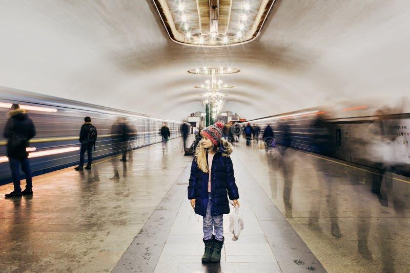 Маленькая девочка стоит на станции метро и ждать стоковые изображения