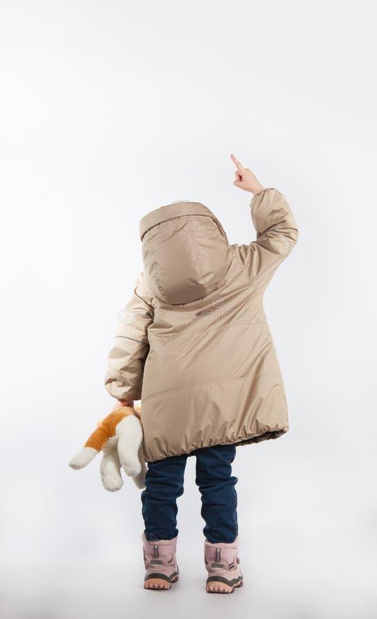 Маленькая девочка стоя с его задняя часть указывая ее палец стоковое изображение