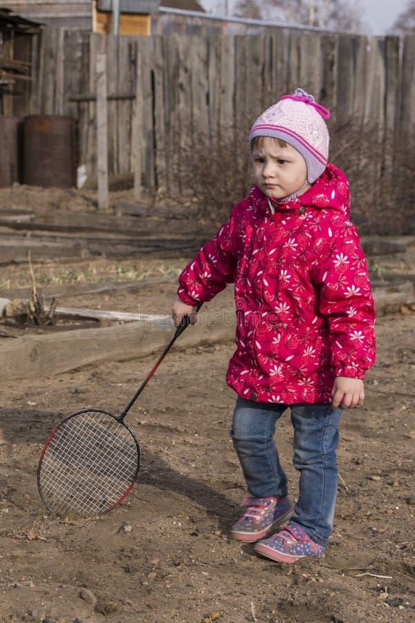 Маленькая девочка стоя с ракеткой тенниса в дворе стоковое фото rf
