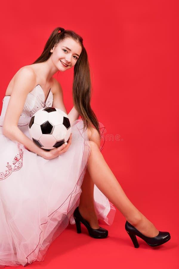 Маленькая девочка с длинными волосами в коротком платье с шариком для играть футбол стоковое фото rf