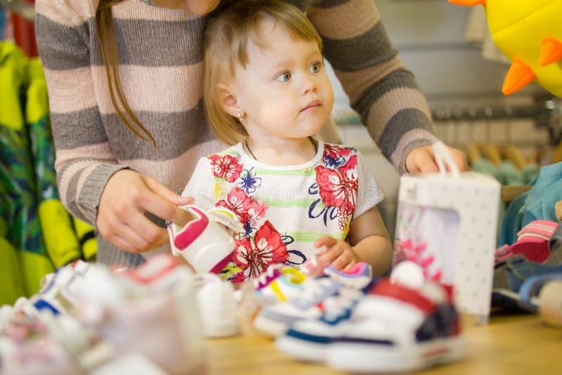 Маленькая девочка с ее мамой на магазине одежды ` s детей стоковые фото