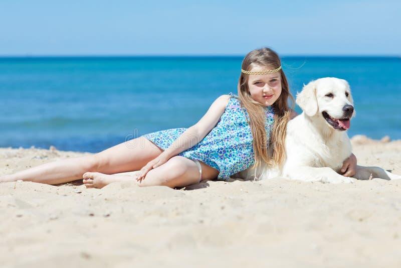 Маленькая девочка с ее собакой взморьем стоковые фото
