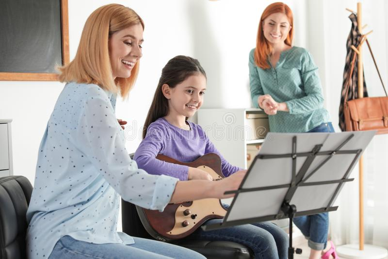 Маленькая девочка с ее учителем и матерью на уроке музыки стоковое фото rf
