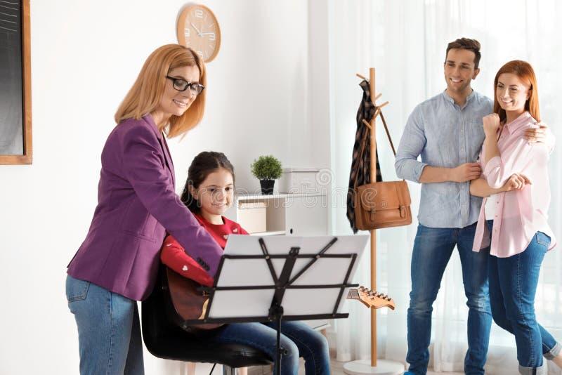 Маленькая девочка с ее учителем и родителями на уроке музыки стоковая фотография rf