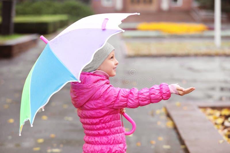 Маленькая девочка с зонтиком в городе стоковые изображения rf