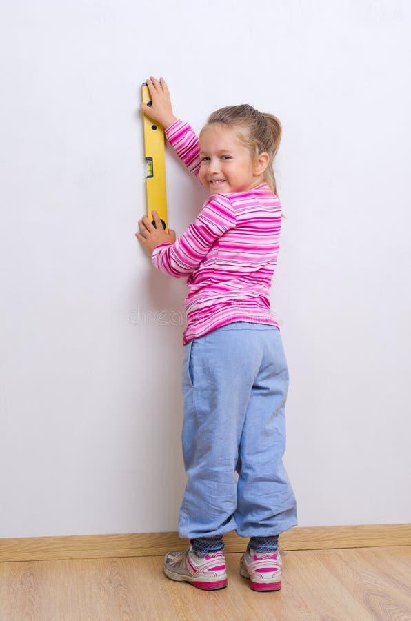 Маленькая девочка с измеряя уровнем стоковое изображение rf