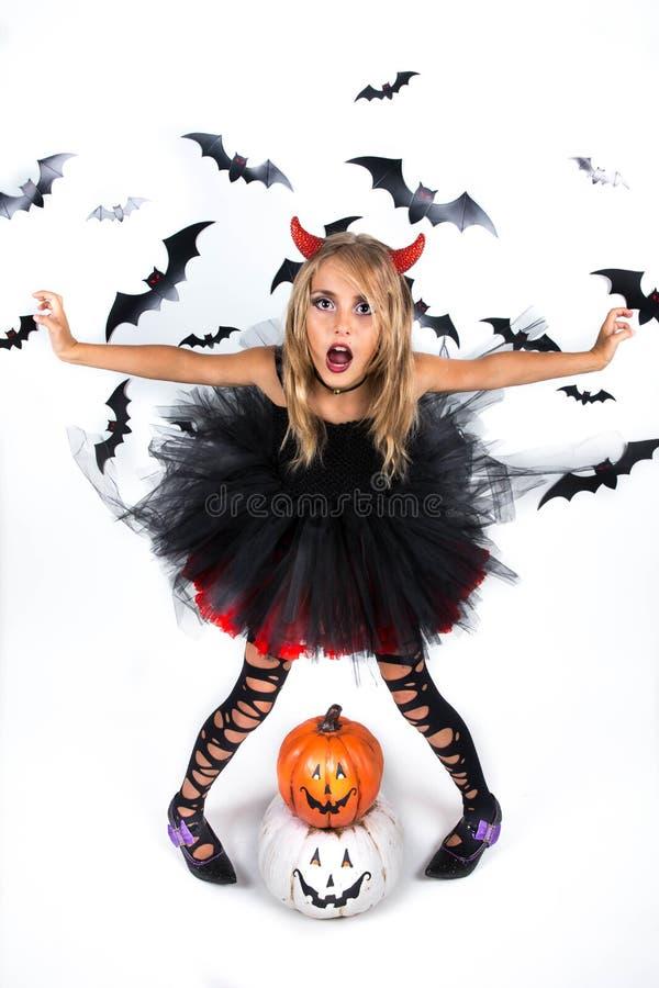 Маленькая девочка с костюмом дьявола демона одевала в черном красном платье и рожки красного дьявола на заплата и хеллоуин тыквы  стоковое фото