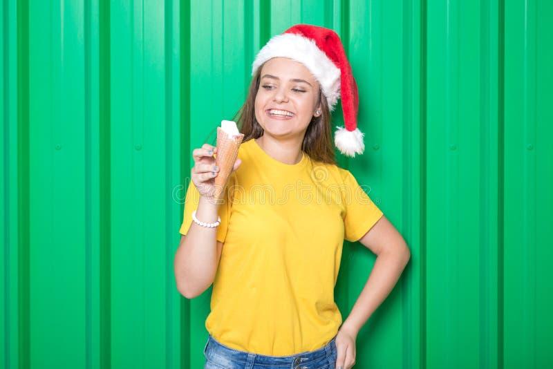 Маленькая девочка с мороженым и шляпой Санта Клауса против зеленой стены Принципиальная схема рождества стоковое фото